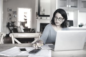 Freelancer working at her dining room table using a calculator and a laptop to balance her budget
