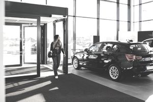 Full length of young woman entering car showroom