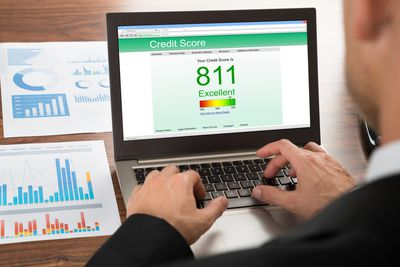 Man checking his FICO credit score online using a laptop