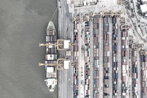 Shipping containers filled with American durable goods being loaded onto a ship in port
