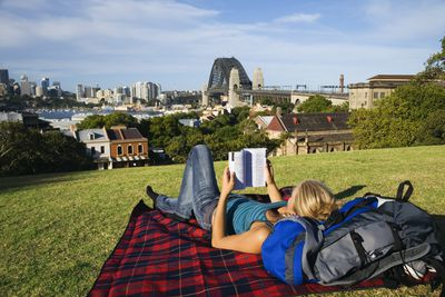 Woman backpacking laying in a park reading