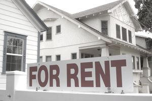 For Rent sign in front of a small white house with blue trim.