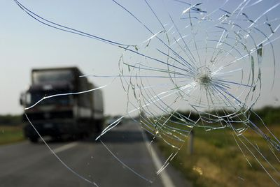 Cracked windshield in need of replacement on highway as truck approaches