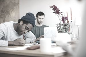 young man in blue beanie studying at table, while another young man in green shirt studies behind him