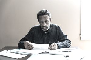 An older man sits at a table, frowning as he looks at a pile of tax paperwork spread out in front of him