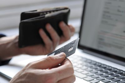 A hand holding credit card and wallet by laptop