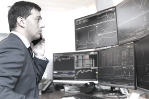 Man on phone trading stocks in front of several computer monitors