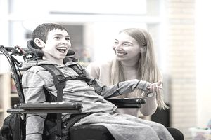 Young boy in wheelchair with special needs laughing with his female caretaker
