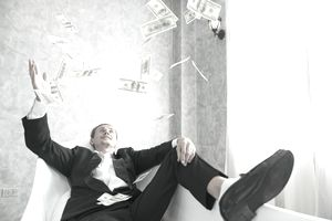 Man lounging in chair tossing his tax refund money into the air
