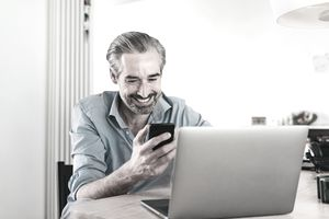 Man looking at phone smiling while sitting in front of laptop