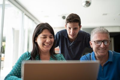 mom, dad, and son standing in living room looking at something on computer