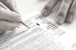 Closeup of a man's hand signing a tax return