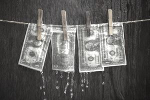 Money hanging on a clothesline dripping with water