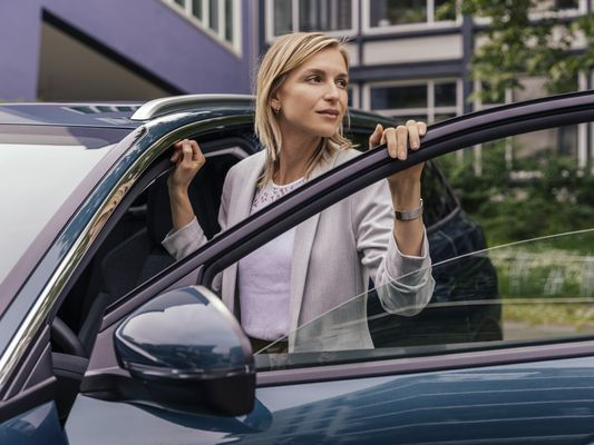 A woman steps into her car.