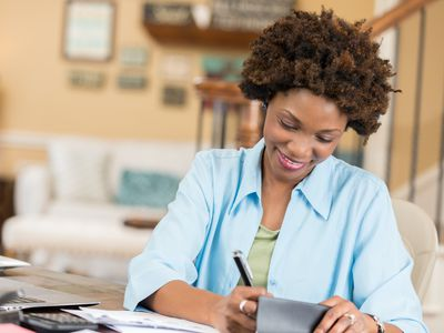 Woman writing a check or balancing her checkbook; bills and documents are on the desk along with a laptop
