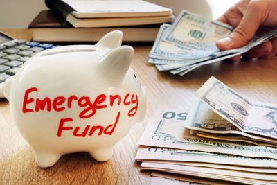 Piggy bank with Emergency Fund written on it surrounded by money
