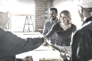 Smiling couple in room under construction shakes hands with contractors
