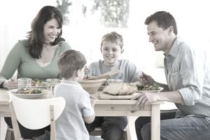 Young family smiling while sharing a meal