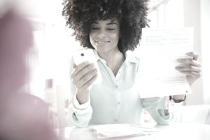 Mixed race woman paying bill with cell phone