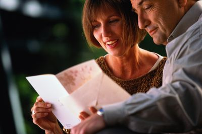 Couple outdoors, woman opening greeting card