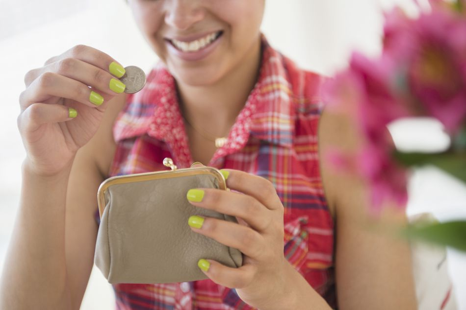 Woman putting money into her wallet insurance savings