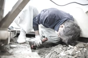 Construction worker in mask uses flashlight to inspect house foundation