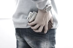 A man is replacing his wallet in his back pocket. The wallet is overflowing with cash.