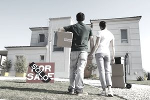 """Rear view of a young couple looking at a house with a """"sold"""" sign in the lawn."""