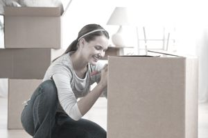 Smiling woman writing on a large packing box