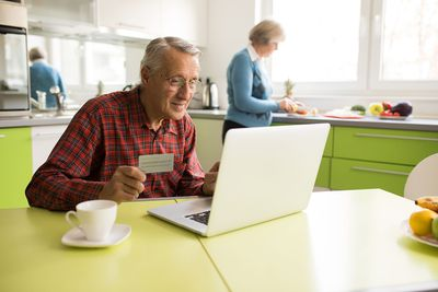 Elderly man on a laptop with credit card in hand