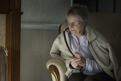 Woman wearing fleece jacket and rubbing hands in her cold home