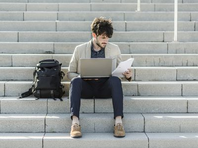 Pensive man with laptop sitting on steps checking documents
