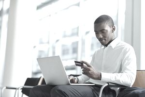 Young man in white shirt sitting at airport making an online purchase with credit card