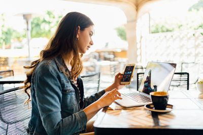 Woman at a cafe checking altcoin value on her phone