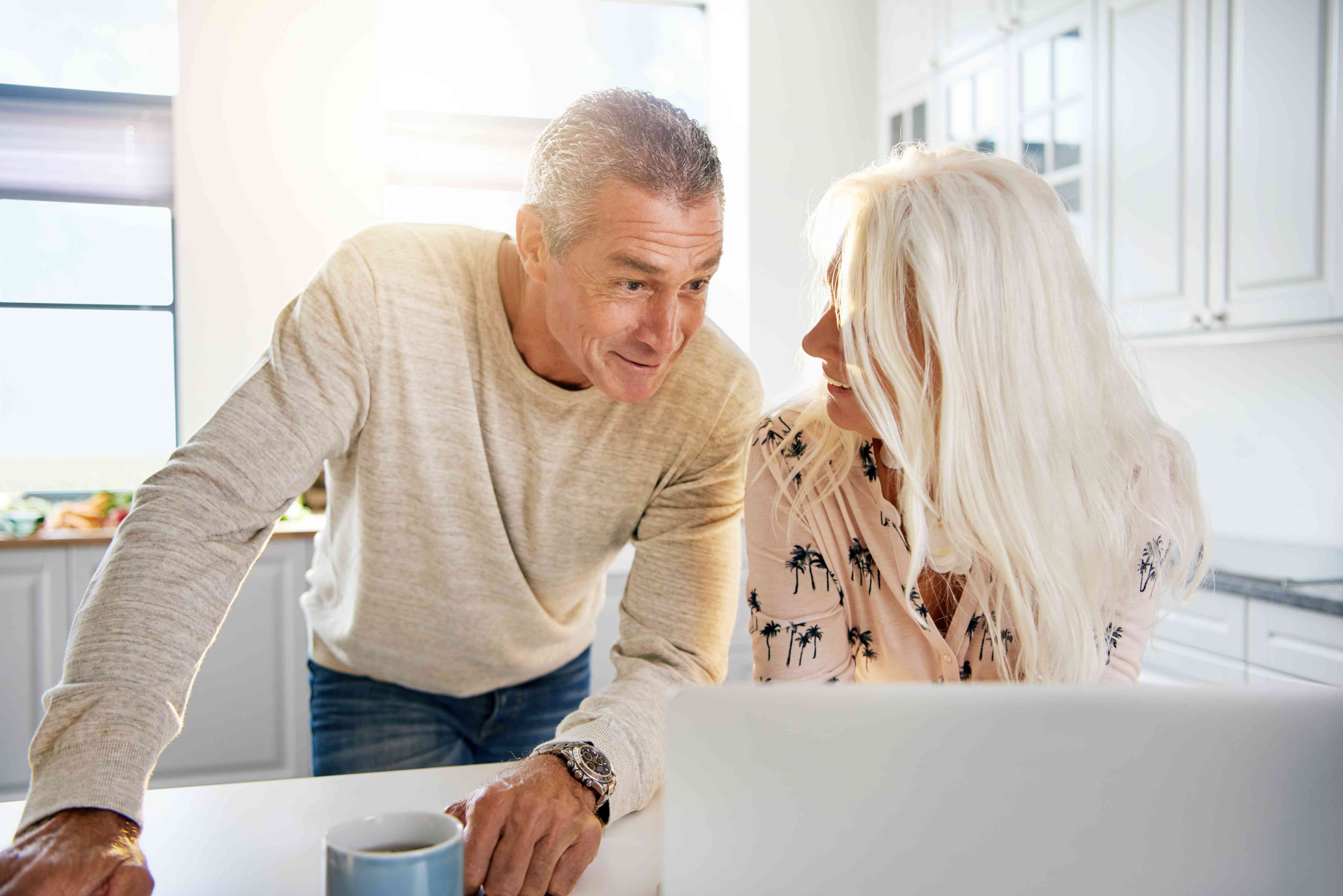 Retired couple in front of a computer pleased to learn that they can roll after-tax 401(K) contributions to a Roth IRA