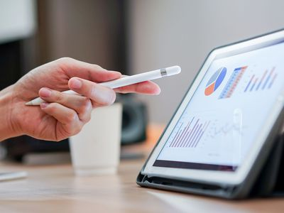 Hand with stylus gesturing to tablet with charts and graphs
