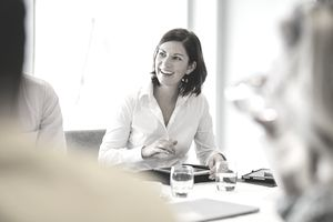 Cheerful mid adult woman smiling at business meeting