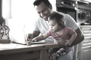 Father and baby girl work at laptop on desk at home