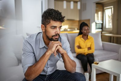 Young Couple Sitting Apart From Each Other in a Living Room, Apparently in an Argument