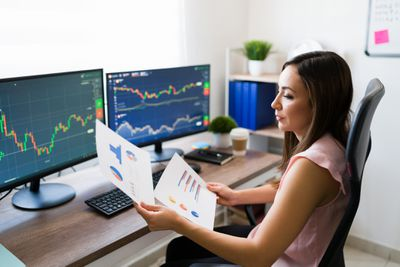 Professional looking at charts and screens to analyze stocks