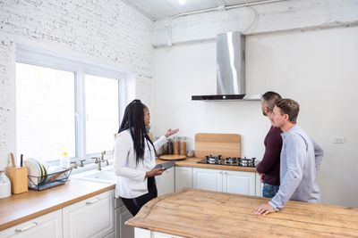 real estate agent showing property owners a new home, standing in the kitchen
