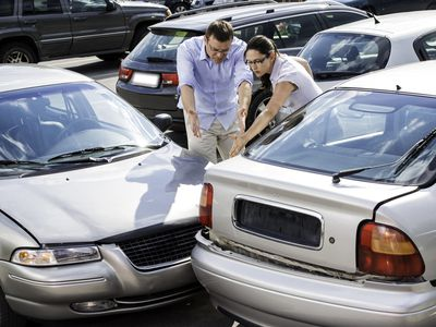 Two people involved in an accident assessing the damages