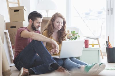 Young couple in new flat with cardboard boxes, using laptop