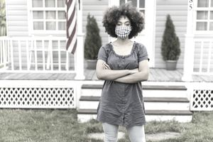Portrait of a young afro woman wearing protective face mask in front of her farmhouse, hands crossed