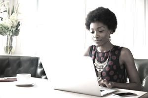 Woman using laptop at table to check her 403b contributions