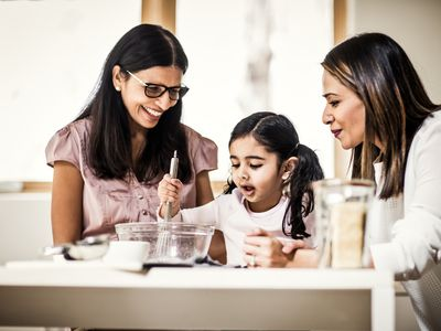 A little girl adds ingredients to a bowl while two women smile at her as they bake together