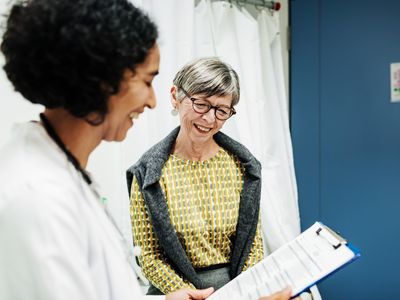 Doctor reviews clipboard with happy female older patient