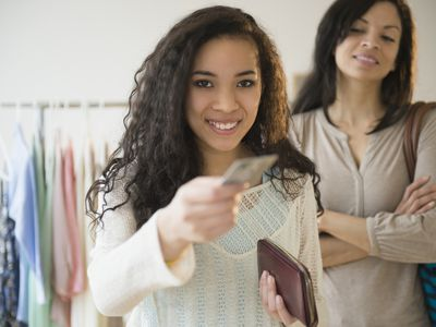 A teenager holds out a credit card for a purchase as an older woman stands in the background.