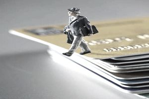 Male figurine reaching the limit of his credit by stepping off the edge of his stack of credit and debit cards