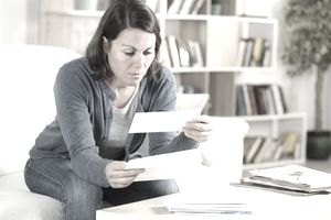 Serious adult woman looking receipts at home